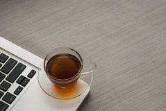 Één die kop thee op laptop wordt geplaatst stock fotografie