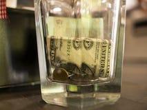 Één dollar en muntstukken in een glas gefacetteerd glas royalty-vrije stock foto