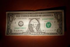 Één dollar met een vlek lichte en donkere sensatie Stock Foto's