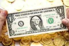 Één dollar op hand en gouden muntstukken Stock Foto