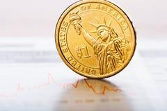 Één dollarmuntstuk op schommelende grafiek Stock Afbeeldingen
