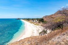 Één dollarstrand Idillic geel zandig strand van Oost-Timor, Timor-Leste Kustlijn met heuvels, bergen en droge savanne stock afbeeldingen