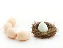 Één ei binnen het nest en andere eieren buiten Stock Foto