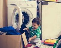 Één en de halve jongen die van de jaren oude baby kleren in wasmachine zetten stock foto's