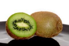 Één en halve kiwi op de zwarte plaat Royalty-vrije Stock Foto