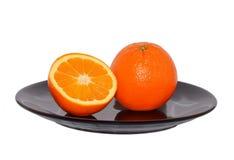 Één en halve sinaasappel op de zwarte plaat Royalty-vrije Stock Foto