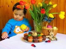 Één-en-helft-jaar-oude jongenszitting bij de Pasen-lijst Stock Afbeelding