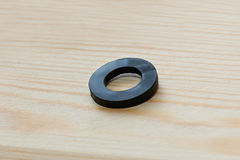 Één enkel rubberverbindingsstuk op een eenvoudige houten achtergrond stock foto