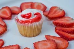 Één enkele cupcake met aardbeiplakken op witte achtergrond stock foto