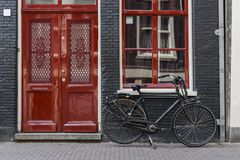 Één enkele fiets buiten een rode deur in Amsterdam royalty-vrije stock afbeelding