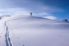 Één enkele mannelijke skiër die van het binnenland langs een lange sneeuwrand ski?en royalty-vrije stock fotografie