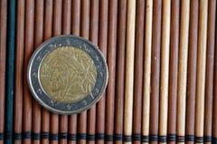 Één euro muntstuk ligt op de houten Benaming van de bamboelijst is 2 euro - achterkant Royalty-vrije Stock Afbeelding