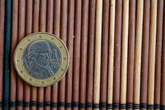 Één euro muntstuk ligt op de houten Benaming van de bamboelijst is 2 euro - achterkant Stock Fotografie