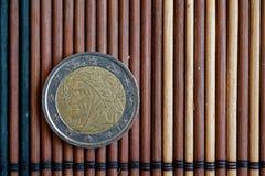 Één euro muntstuk ligt op de houten Benaming van de bamboelijst is twee euro - achterkant Stock Foto
