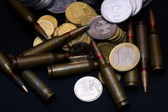 Één euro, Russische roebel en kleine Oekraïense muntstukken met geweer militaire munitie op zwarte achtergrond Symboliseert oorlo royalty-vrije stock foto