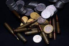 Één euro, Russische roebel en kleine Oekraïense muntstukken met geweer militaire munitie op zwarte achtergrond Symboliseert oorlo royalty-vrije stock fotografie