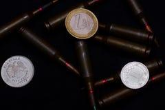 Één euro, één Russische roebel en Oekraïense hryvnamuntstukken met geweer militaire munitie op zwarte achtergrond Symboliseert oo stock afbeeldingen