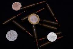 Één euro, één Russische roebel en Oekraïense hryvnamuntstukken met geweer militaire munitie op zwarte achtergrond Symboliseert oo stock afbeelding