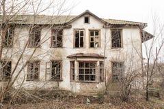 Één foto van een oude en vreselijke verlaten boerderij, die uiteindelijk verslechtert, overwoekerd met oude bomen Leefde hier oud stock fotografie