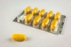 Één gele pillenclose-up op een achtergrond van de verpakking van tabl royalty-vrije stock foto