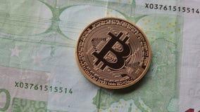Één gouden muntstuk van bitcoin op de achtergrond van euro Stock Foto's
