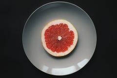 Één grapefruit op grijze plaat op donkere achtergrond Stock Afbeeldingen