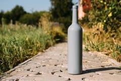 Één grijze fles op de weg van de tegels, het dorp, landelijk alcoholisme, dronkenschap alcoholische ziekte wijn natuurlijke drank royalty-vrije stock foto