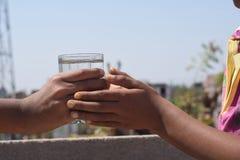 Één hand die water geven aan een dorstige persoon Stock Afbeeldingen