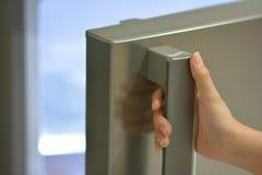 Één hand het openen ijskast Stock Fotografie