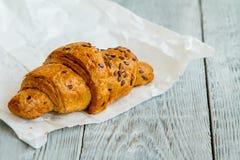 Één heerlijk croissant met gouden korst en bestrooid met zaden op een Witboek royalty-vrije stock foto's