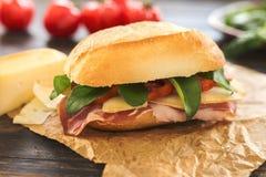 Één heerlijke sandwich op een pakpapierzak met sommige tomaten royalty-vrije stock afbeeldingen
