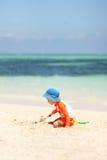 Één het Kaukasische jongen spelen met zand bij tropisch strand royalty-vrije stock afbeeldingen