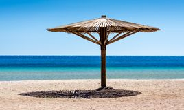 Één houten strandparaplu op het zand op het strand tegen het blauwe water van het Rode Overzees in van Zuid- Egypte Dahab Sinai royalty-vrije stock foto's