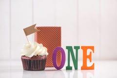 Één jaarverjaardag Heerlijke creatieve cupcake en decoratieve ite Stock Foto