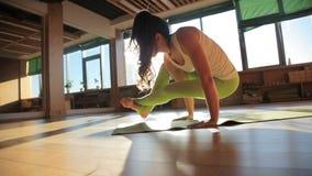 Één jaren '30 persoonlijke trainer die asanas op matwerk in yoga'sstudio doen stock video