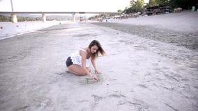 Één jong meisje, die in zand, gevormd hart trekken, in openlucht strand, stock videobeelden