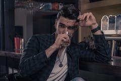 Één jonge knappe mens slechts, kijkt zijdelings het drinken geest alc Royalty-vrije Stock Foto