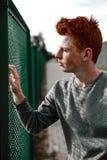 Één jonge knappe rode haired modieuze jongen die zich dichtbij stadion in zonnige dag bevinden openlucht, dragend toevallige kled Royalty-vrije Stock Foto