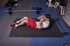 Één jonge mens, abs oefent uit, binnen leggend op vloermat, gymnastiek royalty-vrije stock foto's