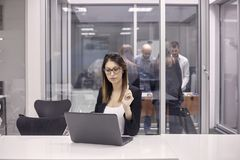 Één jonge vrouw die aan laptop in bureau, groep werken arbeiders die lijstvoetbal in ander bureau spelen stock foto's