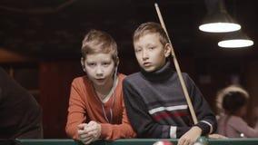 Één Jongen die snooker voorbereidingen treffen te spelen terwijl een andere het luisteren muziek stock videobeelden