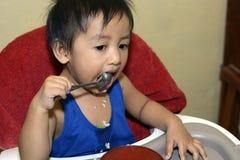 Één jongen die van de 1 éénjarige Aziatische baby zelf door lepel leren te eten, slordig op baby het dineren stoel stock foto's