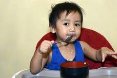 Één jongen die van de 1 éénjarige Aziatische baby zelf door lepel leren te eten, slordig op baby het dineren stoel royalty-vrije stock afbeeldingen