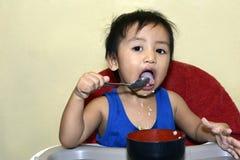 Één jongen die van de 1 éénjarige Aziatische baby zelf door lepel leren te eten, slordig op baby het dineren stoel stock fotografie