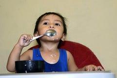 Één jongen die van de 1 éénjarige Aziatische baby zelf door lepel leren thuis te eten, slordig op baby het dineren stoel royalty-vrije stock fotografie