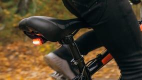 Één Kaukasische de fietsweg van kinderenritten in de herfstpark Het meisje die zwarte oranje cyclus in bosjong geitje berijden ga stock afbeeldingen