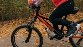 Één Kaukasische de fietsweg van kinderenritten in de herfstpark Het meisje die zwarte oranje cyclus in bosjong geitje berijden ga royalty-vrije stock foto's