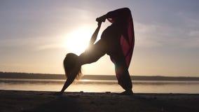 Één Kaukasische vrouw die yoga in openlucht uitoefenen Silhouet op een zonsondergang en een overzees op de achtergrond wordt geïs stock video