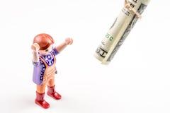 Één kleine persoon en één dollarbankbiljet op een koord, zaken Stock Foto's