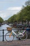Één kleurrijke fiets is op de brug dichtbij het kanaal in Amsterdam stock foto's